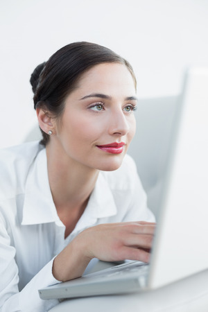 Close-up of a beautiful young woman using laptop at home photo