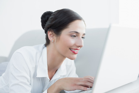 Close-up side view of a beautiful young woman using laptop at home photo