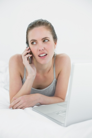 Casual young woman using cellphone and laptop in bed photo