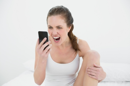 Young woman shouting into mobile phone in bed at home photo