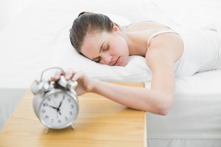 extending: Sleepy woman in bed extending hand to blurred alarm clock at bedroom Stock Photo