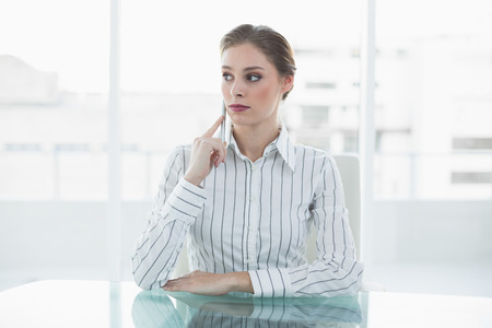 Serious young businesswoman sitting at her desk in her office Stock Photo - 25400977