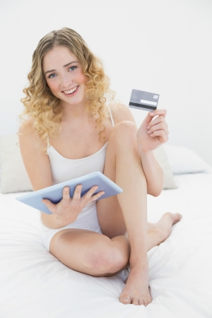 Pretty smiling blonde sitting on bed holding tablet and credit card in bright bedroom photo