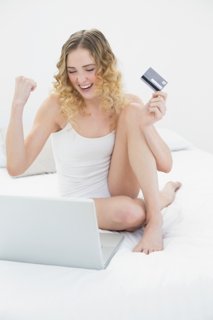 Pretty excited blonde sitting on bed using laptop and credit card in bright bedroom photo