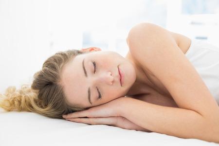slumbering: Pretty content blonde lying in bed slumbering in bright bedroom