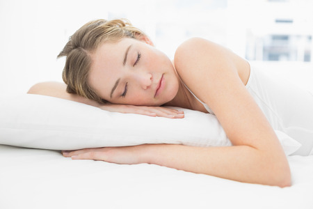 peacefully: Pretty calm blonde lying in bed sleeping peacefully in bright bedroom