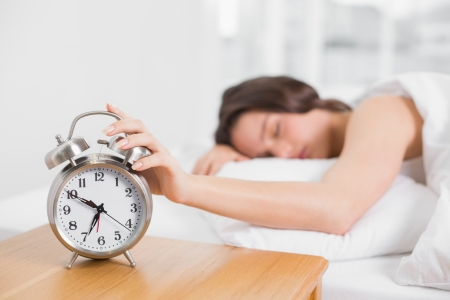 Sleepy blurred young woman in bed extending hand to alarm clock at home