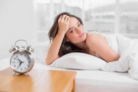 bedside table: Portrait of a beautiful young woman lying in bed with alarm clock on bedside table