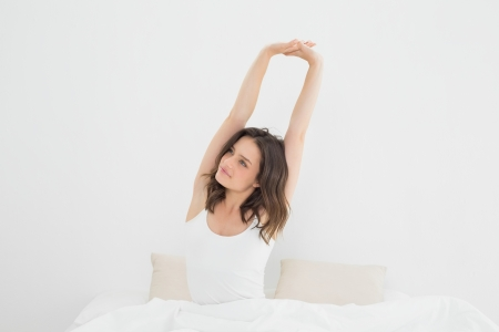 Young woman waking up in bed and stretching her arms photo