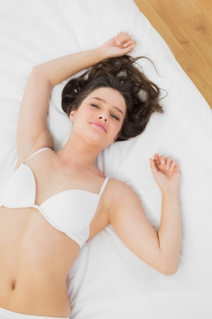 High angle view of a beautiful young woman sleeping in bra on bed photo