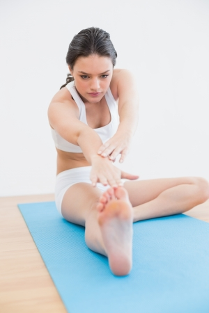 hamstring: Full length of a toned young woman doing the hamstring stretch on exercise mat in fitness studio Stock Photo