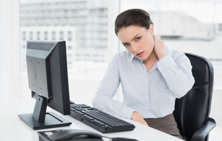 Portrait of a young businesswoman with neck pain sitting at office desk