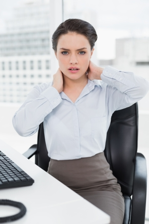 Portrait of a young businesswoman with neck pain sitting at office desk photo