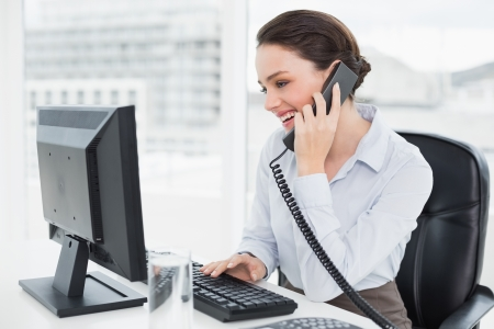 classy woman: Smiling elegant businesswoman using landline phone and computer in a bright office Stock Photo