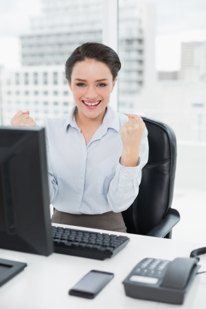 clenching fists: Portrait of an excited businesswoman clenching fists at office desk