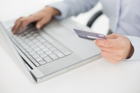 Close-up mid section of a woman doing online shopping through laptop and credit card photo
