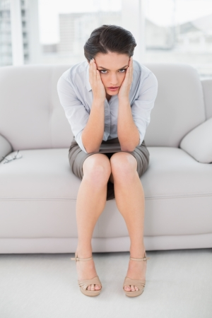 Full length portrait of an elegant young woman sitting with head in hands on sofa at home photo