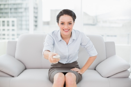 Portrait of a smiling elegant young woman with remote control sitting on sofa at home photo
