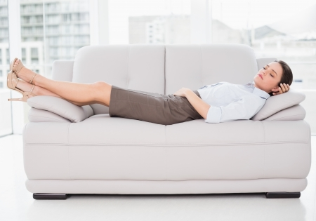 Side view of a well dressed young woman sleeping on sofa at home Stock Photo