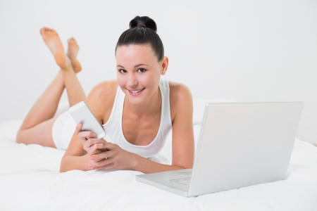 Portrait of a smiling casual young woman using cellphone and laptop in bed photo