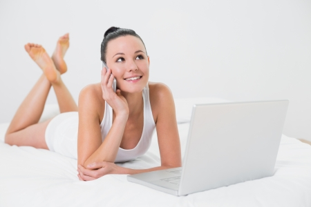 Smiling casual young woman using cellphone and laptop in bed photo