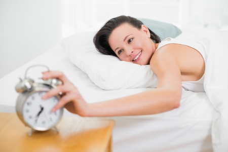 extending: Smiling young woman in bed extending hand to alarm clock at home