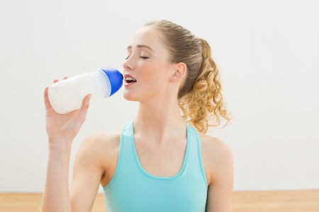 Calm slim blonde sitting on floor drinking from sports bottle in bright room