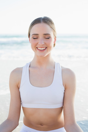 Happy slender woman sitting on the beach peacefully with closed eyes photo