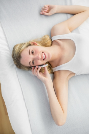 Content peaceful woman phoning with her smartphone while lying on her bed smiling at camera photo