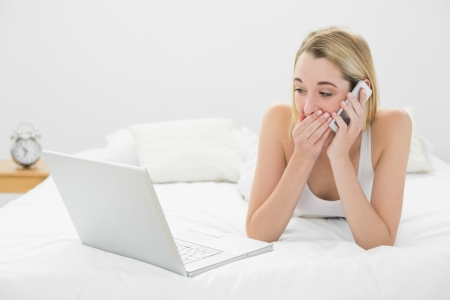 Beautiful shocked woman phoning while lying on her bed looking at laptop at home photo