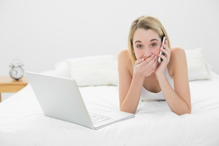 Young surprised woman phoning while lying on her bed next to her notebook looking at camera photo