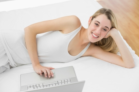 Cheerful blonde woman using her notebook smiling at camera lying on her bed photo