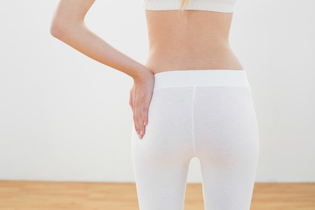 salle de sport: Mi, section sur la femme �lanc�e posant en tenue de sport avec la main sur la hanche debout dans la salle de sport