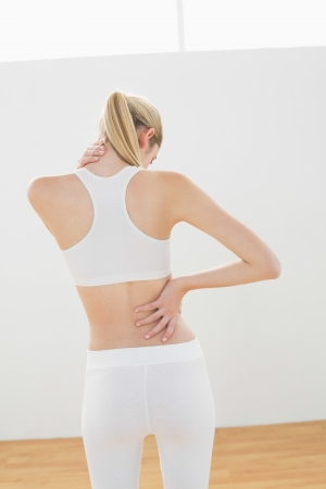 Sporty blonde woman touching her injured nape standing in sports hall photo