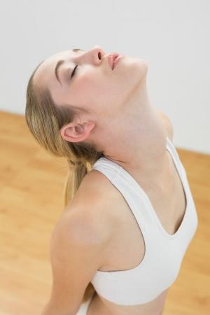 salle de sport: Belle femme sportive qui s'�tend � genoux sur le plancher dans la salle de sport avec les yeux ferm�s Banque d'images