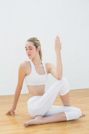 Concentrating ponytailed woman stretching her body sitting on floor in sports hall photo