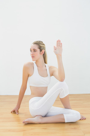 Focused toned woman stretching her body sitting on sports\ floor