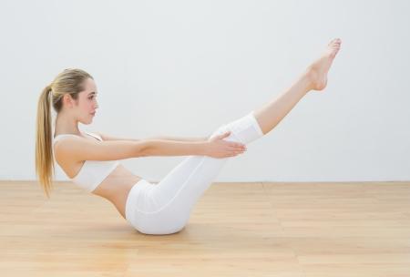 salle de sport: Sporty jeune femme faire de l'exercice des sports assis sur le plancher dans le hall de sport