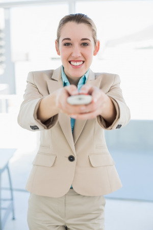 Attractive businesswoman holding a remote smiling cheerfully at camera standing in her office photo