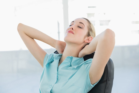 Beautiful peaceful businesswoman relaxing on her swivel chair with eyes closed photo