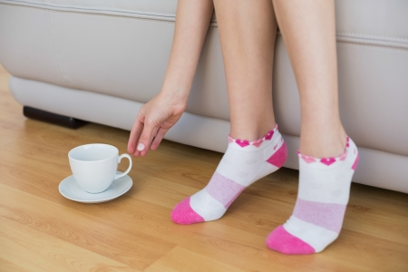 Young slender woman wearing pink socks sitting on couch reaching for a cup Stock Photo - 25433160