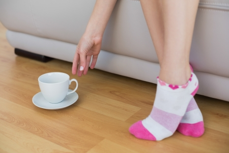 Young slim woman wearing pink socks reaching for a cup sitting on couch Stock Photo - 25433173