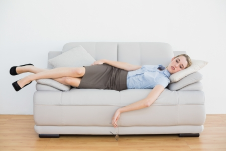 Calm chic businesswoman sleeping while lying on her couch in the office photo