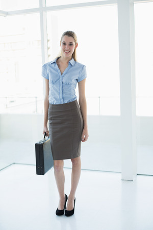 Attractive classy businesswoman posing holding a briefcase smiling at camera photo