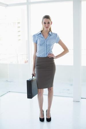 Cute chic businesswoman posing with hand on hip holding a briefcase looking at camera photo