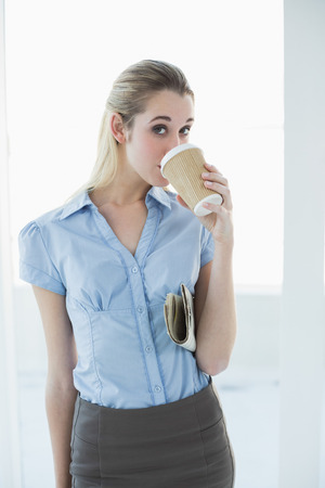 Content chic businesswoman drinking of disposable cup holding a newspaper looking at camera photo