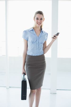 Calm content businesswoman holding her smartphone and briefcase smiling at camera photo