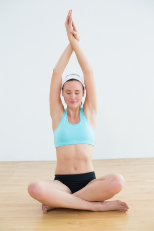 Portrait of a young woman sitting in Namaskar pose with twisted hands and eyes closed at fitness studio photo