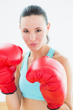 Close-up portrait of a beautiful young woman in red boxing gloves at fitness studio photo