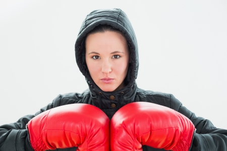 Close up portrait of a beautiful young woman in hood and red boxing gloves photo